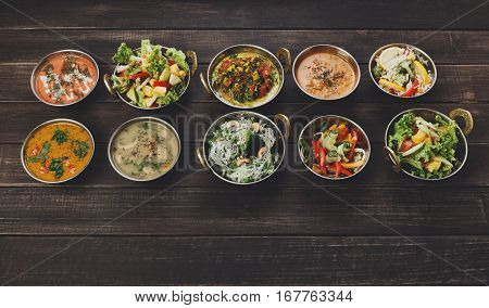 Vegan or vegetarian restaurant dishes top view, hot indian soups, curry, rice and salads in copper bowls. Traditional indian cuisine meal assortment on wood background. Healthy eastern local food