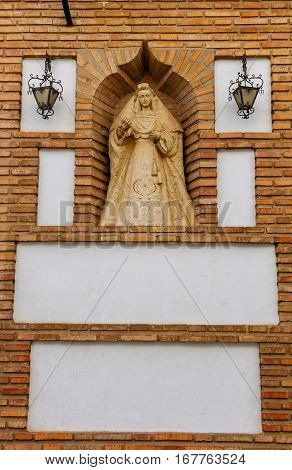 Stone altar with the figure of the saint protector of the Virgin in a street of Cordoba.