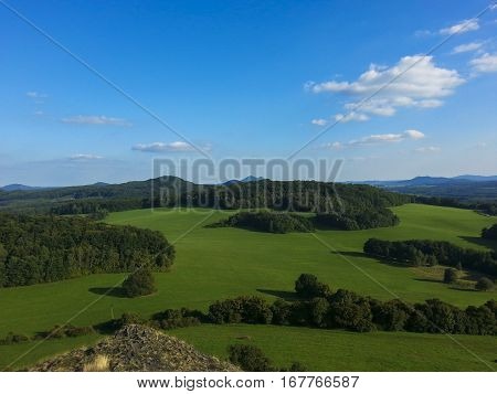 The landscape with green meadow, forest, trees, hills and clear blue sky with a few clouds.