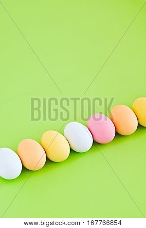 Diagonal row of colorful decorated eggs on a greenery background. Pastel colors. Easter card. Negative space