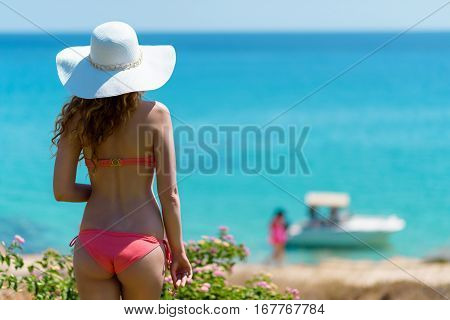 Young woman at the beach. Portrait of a girl in white hat looking at the boat on the sea. Beautiful Summer sea side beach with turquoise water. View from behind