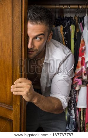 Sexy handsome young man, maybe a lover hiding, standing shirtless with a shirt draped over his shoulder peering out of a walk in closet with a smile as he watches something outside with a leer