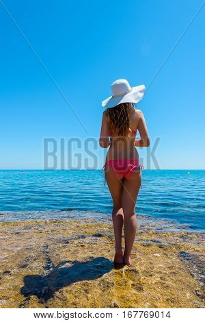 Young woman on the coast of the island. Portrait of a girl in white hat looking at the sea. Beautiful Summer sea side with turquoise water. Cyprus island, Protaras. View from behind