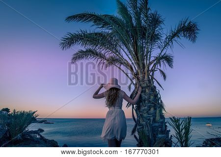 Girl watching sunset view over the sea. Woman in a light summer dress standing by the Palm tree enjoying the view. Cyprus island on a windy day