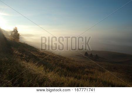 Beautiful sunrise in russian village. Foggy morning.