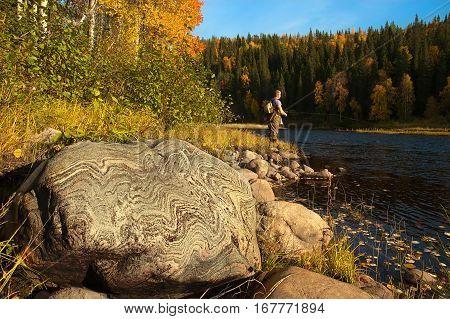 A big stone with beautiful pattern. Fisherman on background.