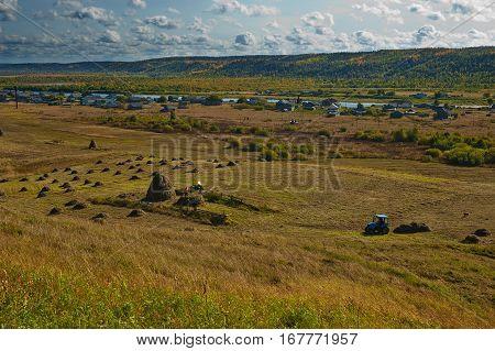 A haymaking in russian village. Beautiful fall landscape.