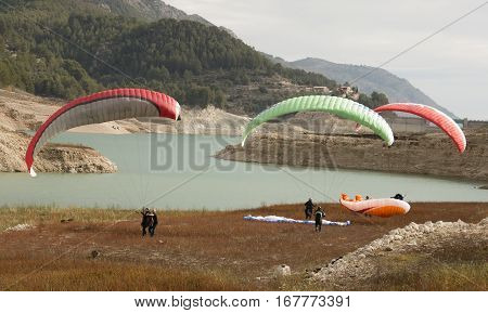 Group of paraglider pilots practicing groundhandling in a valley