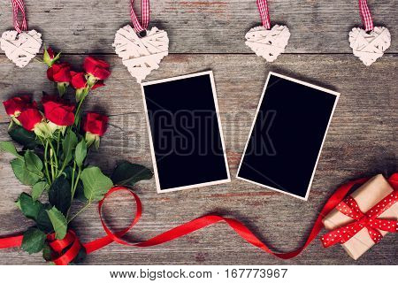 blank photo frames red roses flowers red ribbon and gift box on rustic wooden background. top view. valentines day background. vintage toning