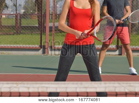 Couple Playing Doubles At The Tennis Court. Close Up Picture Bodies Only