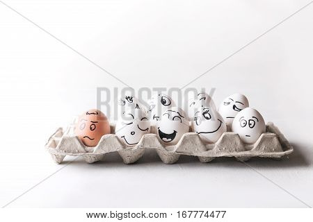 Eggs with funny faces in the package on a white background.  Eggs. Faces on the eggs