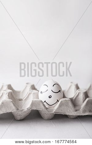 Chicken egg with a pretty funny face in a box on a white background. Easter Concept Photo. Eggs. Faces on the eggs Eggs. White chicken egg sleeping with happy face