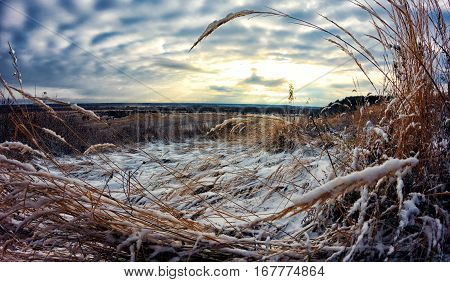 Autumn meets winter. The grass-strewn snow. Sunset sky.