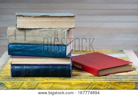 Stack of old hardback books on wooden table. English textbook. Back to school. Copy space.
