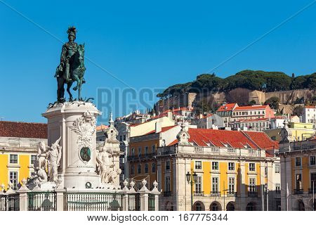 Bronze statue of King Jose on the horse as old colorful houses on background under blue sky at Commerce Square in Lisbon, Portugal.