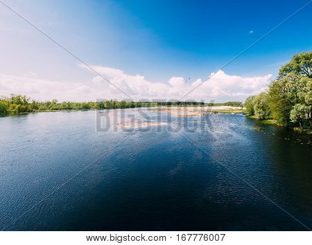 Panorama Of River Or Lake Landscape. Ripple Surface Of Calm Water At Sunny Day. Forest On Other Side. Nature Of Eastern Europe