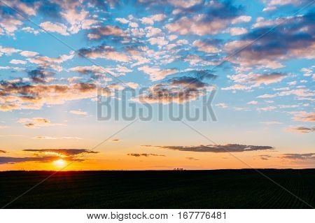 Natural Sunset Sunrise Over Field Or Meadow. Bright Dramatic Sky And Dark Ground. Countryside Landscape Under Scenic Colorful Sky At Sunset Dawn Sunrise. Skyline, Horizon. Warm Colours.
