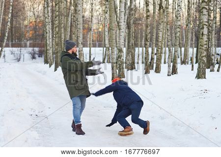Two young modern man while walking through a birch forest in winter. One of them slipped and lost his balance his friend held out his arms. Freeze frame before falling into the snow.
