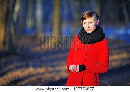 Gorgeous portrait of a young confident girl with gray eyes in a red coat and black scarf at the neck posing in the bright sun on a blurred background of trees in a Park closeup.
