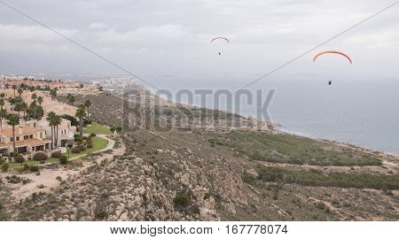 Paragliders soaring by sea cliffs at Santa Pola