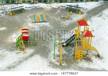 Outdoor children playground with many space for children in winter. Playground equipment in the park.