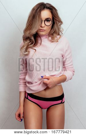 emotions people beauty and lifestyle concept - Sexy Slim Brunette Girl on a gray background a girl in a pink sweater and pink shorts and sunglasses. Party fashion style