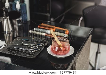 Close up of scissors, combs and hair gel on table at beauty salon