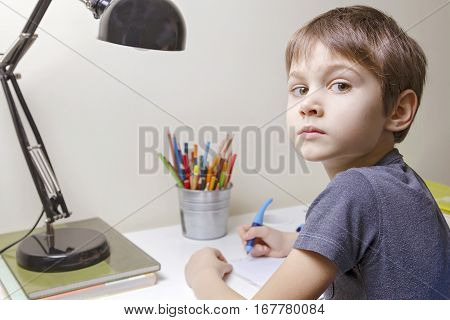 Child reading. Boy sitting at the desk at home and doing his homework. School, children, education concept