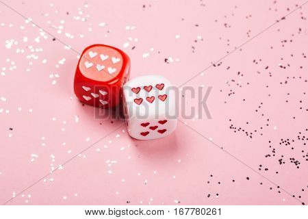 Two dices with hearts on pink background with little silver sparkles.