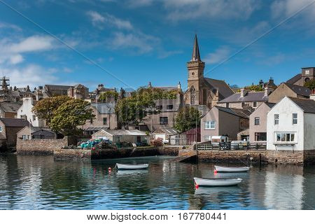 Orkneys Scotland - June 5 2012: View on the old cluttered docks with parish church towering over gray and brown houses under blue sky. Sloops reflecting on sea water. Green vegetation.