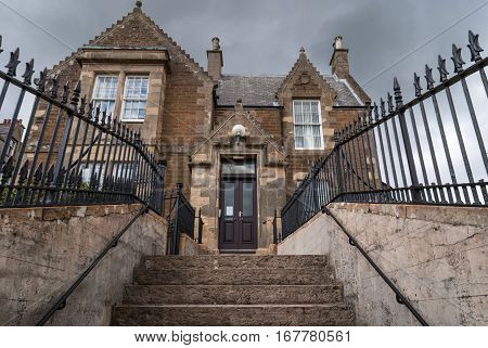 Orkneys Scotland - June 5 2012: The facade of Stromness town hall which stands up a flight of stairs. Brown and gray building under dark cloudy skies. Black fence and gray stone stairs.