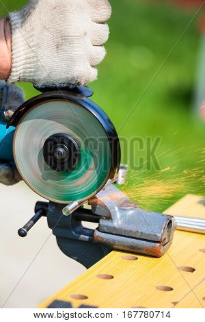 Metal worker cutting metal with angle or disc grinder outdoor