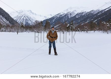 Man Rejoices In The Snow Against The Backdrop Of Mountain Scenery.