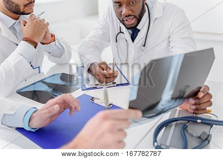 Confident african man is holding x-ray picture and explaining his ideas to colleagues. Other doctors are sitting and listening to him attentively
