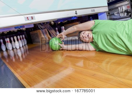 Young Man Sliding Down A Bowling Alley