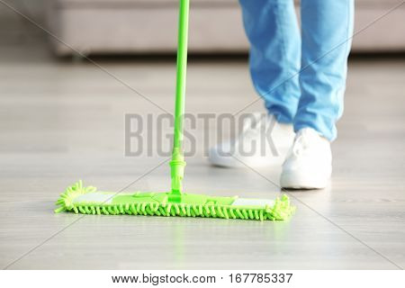 Close up view of woman moping floor at home