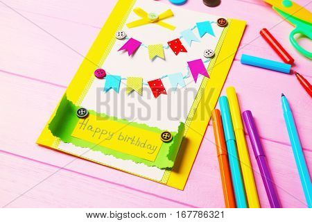 Handmade gift card and colorful felt tip pens on pink wooden background