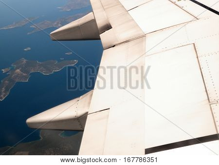 Detail of airplane wing flying above beautiful Greek islands
