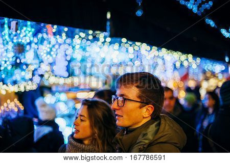 STRASBOURG FRANCE - DEC 20 2016: French couple visiting the Strasbourg Christmas Market with beautiful bokeh lights in the background. Strasbourg Christmas market is considered to be the oldest in the world