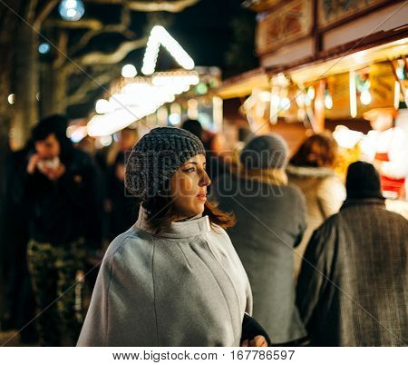 STRASBOURG FRANCE - DEC 20 2016: French woman walking between rows of selers at the Christmas MArket of Strasbourg Frnace