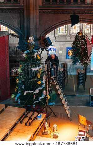 MULHOUSE FRANCE - DEC 12 2015: Temple Saint-Etienne Church Cathedral (Protestant St. Stephen's Church) being prepared by priest for Christmas with Christmas Tree being decorated and lights being arranged - elevated view