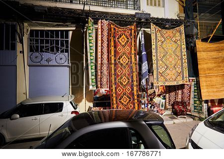 ATHENS GREECE - 26 MAR 2016: Shopping street at night in Athens selling carpets and other knitted carpentry - no tourists no sales