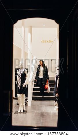 STRASBOURG FRANCE - DEC 20 2016: Woman descending stairs of an Escada store with shopping bags full with luxury clothes. Escada SE is a German luxury women's designer clothing company headquartered in Munich owned by Megha Mittal.