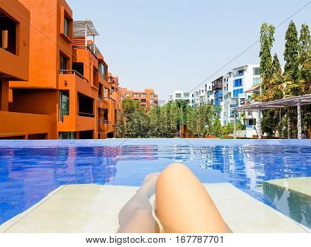 Woman lying on a lounger by the pool at the hotel. Girl at travel spa resort pool. Summer luxury vacation.