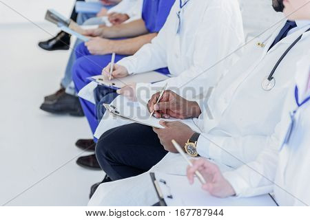 Close up of doctors arms writing on papers with concentration. They are sitting in row during symposium