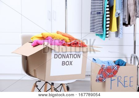 Donation box with clothing on chair