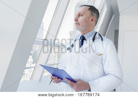 Smart senior general practitioner is thinking about state of patient. He is holding folder of documents and looking through window pensively
