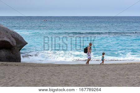 ADEJE, TENERIFE, SPAIN - DECEMBER 2015: Father and daughter are walking along sandy beach of Adeje town on Tenerife isla