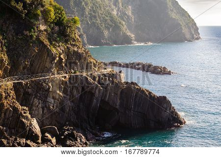 Traveler footpath over water on rocks of Cinque Terre national park near Vernazza town in Italy