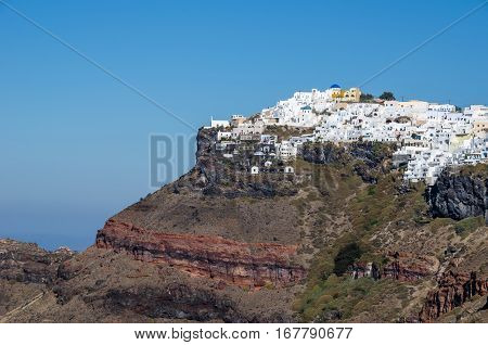 View of Thira the greek town on the volcanic island Santorini with its traditional white houses placed on the top of a conical mountain revealing its volcanic structure
